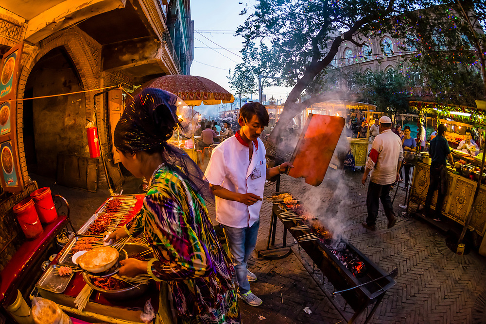 Street vendors cooking kebabs in the night market in the bazaar in Kashgar an oasis city in Xinjiang Province, China.  It is the westernmost city in China, located near the border with Afghanistan, Kyrgyzstan, Pakistan, and Tajikistan. It was a stop on the Silk Road. Uyghur people are a Central Asian people of Muslim Turkic origin. They are China's largest minority group.