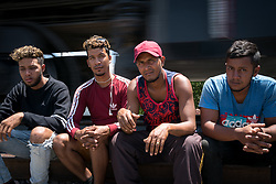 A group of migrant workers sit on the sidings as a train passes. They are waiting for a train heading north. They are part of a group of 12 migrants who are all from the same neighbourhood in the same town in San Francisco Morazán, Honduras. Everyone in the group has worked in at least one trade, and they are hoping to find work in the US.