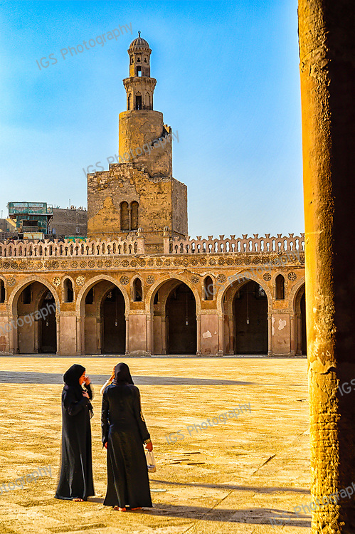 Worshippers standing in the courtyard of the Ibn Tulun Mosque, in front of the unique spiral minaret of the Mosque