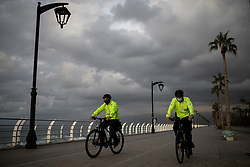 © Licensed to London News Pictures. 15/01/2021. Beirut, Lebanon. Police officers on bicycles patrol the near-empty  Corniche in Beirut on the second day of an 11 day curfew (from 14 Jan to 25 Jan) in an attempt to control a rapid increase in rates of COVID-19 Coronavirus in the country. Today, Lebanon registered two record-breaking statistics, with 6154 cases of Coronavirus, and 44 deaths in the past 24 hours. Photo credit : Tom Nicholson/LNP