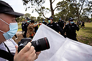 MELBOURNE, VIC - SEPTEMBER 19: Police detain a protester with a banner as press photographers shoot the chaos during the Freedom protest on September 19, 2020 in Melbourne, Australia. Freedom protests are being held in Melbourne every Saturday and Sunday in response to the governments COVID-19 restrictions and continuing removal of liberties despite new cases being on the decline. Victoria recorded a further 21 new cases overnight along with 7 deaths. (Photo by Dave Hewison/Speed Media)