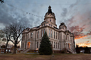 """The sun sets behind Parke County Courthouse, 116 West High Street, Rockville, Indiana 47872, USA. The mansard roofs on the corner and central pavilions characterize the Second Empire style of the Court House, which was designed by Thomas J. and Brentwood Tolan and constructed 1879-82. Indiana limestone faces the structure which rests upon a foundation of native sandstone. The domed tower, rising from the center of the roof, displays a clock on each side. Classical elements such as columns and pediments further adorn the entryways. Parke County is the """"Covered Bridge Capital of the World."""""""