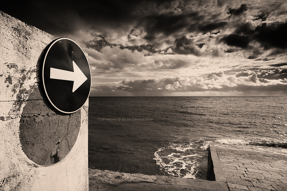 Honourable Mention in the 'Fine Art' category of the 2019, International 14th Black & White Spider Awards<br /> <br /> So strange and funny, to see the One Way road sign directing cars to the open Atlantic Ocean. I love crazy juxtapositions like this.