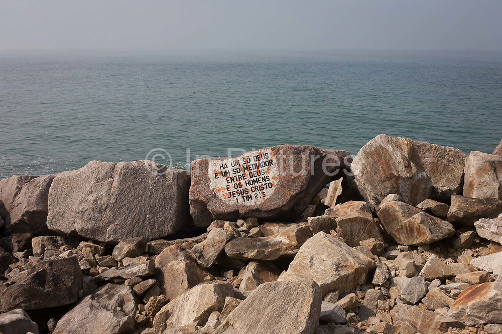 Translated into Portuguese is religious Bible scripture from Timothy 2:5 and painted onto a rock that forms part of the breakwater, on 18th July 2016, on Paredao da Praia da Barra, at Barra, near Aveira, Portugal. In English, it reads: For there is one God and one mediator between God and mankind, the man Christ Jesus.