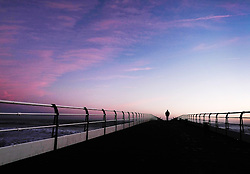 © Licensed to London News Pictures. <br /> 03/10/2016. <br /> Saltburn-by-the-Sea, UK.  <br /> <br /> A man walks along the pier at dawn under pink clouds on a cold October morning at Saltburn-by-the-Sea.<br /> <br /> Photo credit: Ian Forsyth/LNP