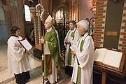 Aartsbisschop Joris Vercammen staat met de nieuwe pastoors bij het doopvont. Op zondag 31 oktober is in de Getrudiskathedraal in Utrecht  Annemieke Duurkoop (rechts) als eerste vrouwelijke plebaan van Nederland geïnstalleerd. Duurkoop wordt de nieuwe pastoor van de Utrechtse parochie van de Oud-Katholieke Kerk (OKK), deze kerk heeft geen band met het Vaticaan. Een plebaan is een pastoor van een kathedrale kerk, die eindverantwoordelijk is voor een parochie. Eerder waren bij de OKK al twee vrouwelijk priesters geïnstalleerd, maar die zijn geen plebaan.<br /> <br /> Archbishop Joris Vercammen is installing two new pastors. At the St Getrudiscathedral in Utrecht the first female dean of the Old-Catholic Church (OKK), Annemieke Duurkoop, is installed together with a new pastor Bernd Wallet. The church has no connections with the Vatican.