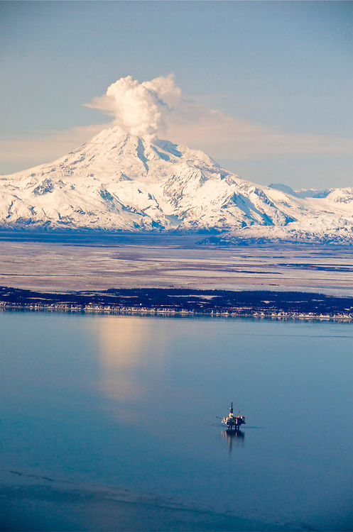 Alaska, Cook Inlet. Redbout volcano aerial with offshore oil platforms in Cook Inlet. Steam plume is visible from the mountain.