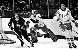 Seals vs. Buffalo Sabres. Jacques Richard, scates past <br />goalie Gary Simmons and Jim Neilson. (1975 photo/Ron Riesterer)