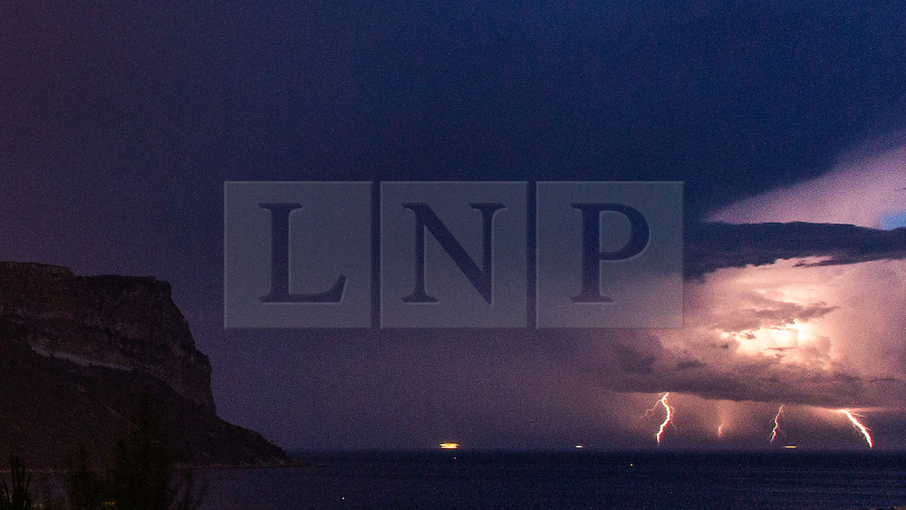 © Licensed to London News Pictures . 03/08/2014 . Cassis , France . A ship passes through a thunderstorm , the sea around struck by bolts of lightning , as intense electrical storms sweep the South of France this morning ( Sunday 3rd August 2014 ) . Viewed from the historic town of Cassis , near to Marseille in the South of France , the vulnerable vessel is seen steaming straight in to the path of the storm in the Mediterranean Sea and , at one point , appears to be struck by lightning . In the left of the frame , the silhouette of the 1293 foot high Cap Canaille cliff - the highest sea cliff in Europe . Photo credit : Joel Goodman/LNP