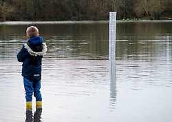 © Licensed to London News Pictures. 03/01/2021. Oxford, UK. A boy looks at a monolith which has appeared in a flooded Oxford park. The object appeared overnight in Oatlands Park, West Oxford. It follows the appearance of similar monoliths in parts of the UK and around the world. Photo credit: Andre Camara/LNP