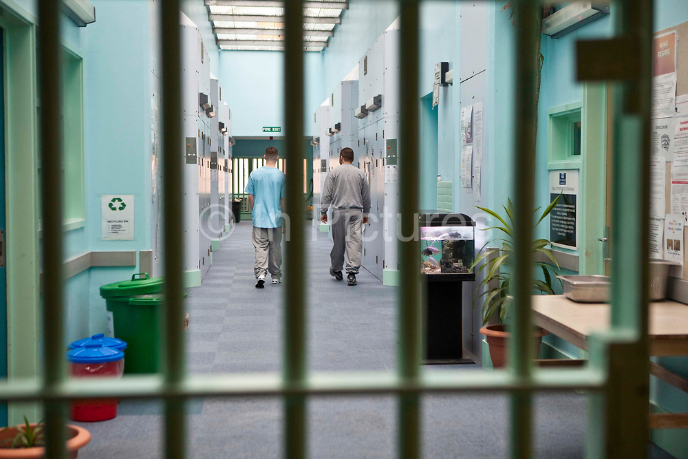 'Enhanced' prisoners walking down the corridor of H wing at the Young Offenders Institution  in Aylesbury, United Kingdom.  Under the Incentives and Earned Privilege Scheme, prisoners in the U.K. can earn extra privileges for good behaviour such as wearing their own clothes, having televisions in their cells, and having more free time to socialise.  They are often housed together in their own wing.  There are three levels of earned privileges - Basic, Standard and Enhanced.
