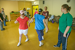 Group of Day Service users with learning disability enjoying a line dancing class encouraged by Day Service Officer,