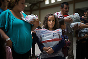 An eight-year-old girl from Honduras seeking asylum holds a Homeland Security bag as her family is released from ICE detention with other undocumented immigrants at a bus depot in McAllen, Texas, U.S., July 27, 2018.