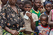 A girl holding a UNHCR issued card waits in line to receive coupons during a non-food item fair at the Miketo IDP settlement, Katanga province, Democratic Republic of Congo on Sunday February 19, 2012. Displaced people who have lost most of their belongings as they fleed their homes receive coupons their can exchange for goods at a fair held in partnership with local traders.