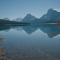 Mountains reflect in Bow Lake in Banff National Park, Alberta, Canada.