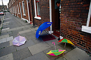 A father looks down at four coloured umbrellas that have been left by children on the pavement outside a terraced street in Belfast. Having played then finished with the waterproof items the kids have simply abandoned them on the paving stones as a man who might be a father looks down, deciding whether to pick them up himself and order the kids to do it themselves. Into the distance are identically designed Victorian terraced houses still used by families in this British province of Northern Ireland?