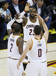The Cleveland Cavaliers' LeBron James celebrates with teammates Kyrie Irving (2) and Kevin Love (0) in the first quarter during Game 4 of the NBA Finals at Quicken Loans Arena in Cleveland on Friday, June 9, 2017. (Photo by Leah Klafczynski/Akron Beacon Journal/TNS) *** Please Use Credit from Credit Field ***