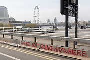 The London skyline beyong graffiti on Waterloo Bridge on day 4 of protests by climate change environmental activists with pressure group Extinction Rebellion, on18th April 2019, in London, England.