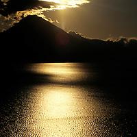 Americas, Central American, Guatemala, Lake Atitlan. A setting sun shines on Lago Atitlan in Guatemala.