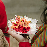 A woman brings offering of petals on a silver plates. Second day of the wedding, Puja ceremony and Saipata gifts are taken to the bride's home.