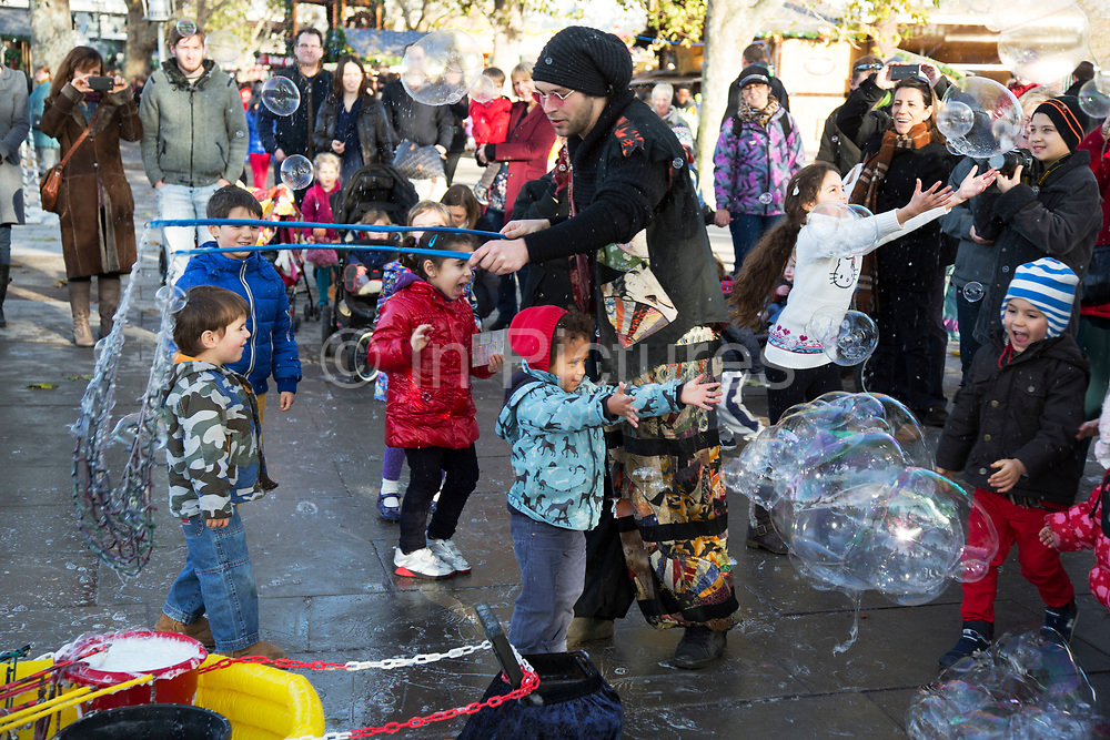 Bubble performer delights the children on the South Bank, London. These bubble blowers are a common site making complex and large bubbles to delight audiences. The South Bank is a significant arts and entertainment district, and home to an endless list of activities for Londoners, visitors and tourists alike.