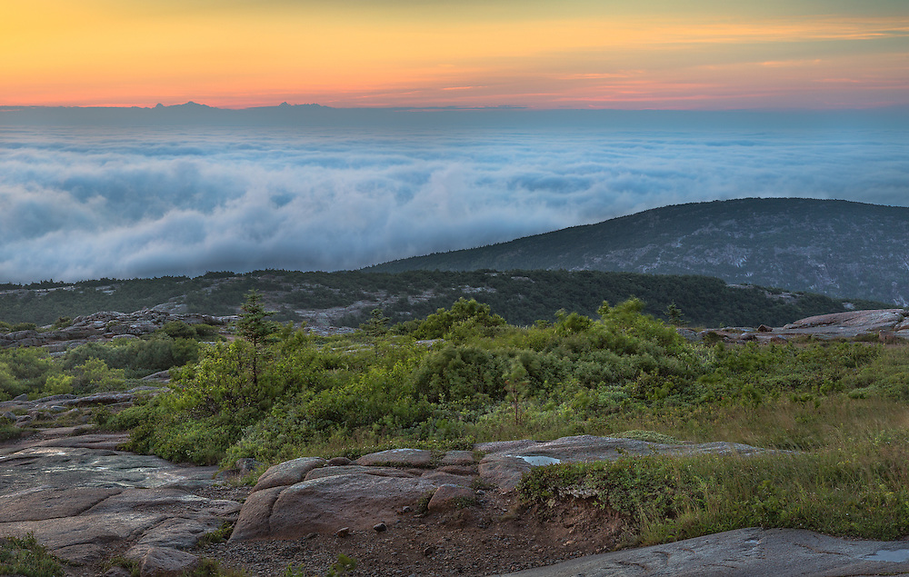 A sea of fog blankets the view to the east at the summit of Cadillac Mountain just before sunrise.