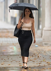 © Licensed to London News Pictures. 13/08/2020. London, UK. A woman carrying an umbrella makes her way through a downpour of rain on Kensington High Street, West London as the UK experiences thunderstorms and heavy rainfall following days of sunshine and high temperatures. Photo credit: Ben Cawthra/LNP