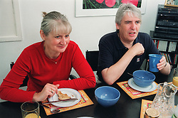 Man and woman sitting at table eating breakfast,