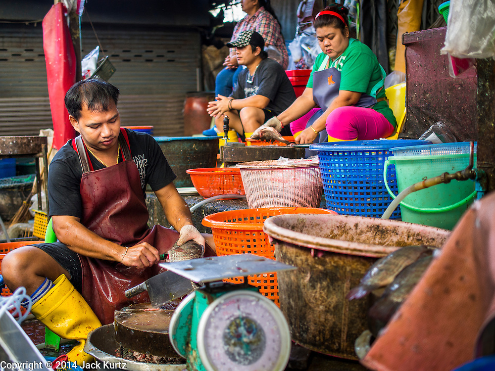 19 NOVEMBER 2014 - BANGKOK, THAILAND: Fish sellers in Khlong Toei Market in Bangkok. Between July and September the economy expanded just 0.6 percent compared to the previous year, the National Economic and Social Development Board (NESDB) reported. Thailand's economy achieved a weak 0.2 per cent growth across the first nine months of the year. The NESDB said the Thai economy is expected to grow by 1 percent in 2014. Authorities say the sluggish growth is because tourists have not returned to Thailand in the wake of the coup in May, 2014, and that reduced demand for computer components, specifically hard drives, was also hurting the economy. Thailand is the leading manufacturer of computer hard drives in the world. The Thai government has announced a stimulus package worth $11 billion (US) to provide cash handouts to farmers and promised to speed up budget spending to boost consumption.   PHOTO BY JACK KURTZ