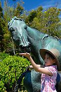 Child (6 years old) feeding bronze mare (La Reyna) by the French artist, Arthur J. le Duc. Royal Botanic Gardens, Sydney, Australia
