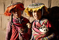 2 young quechua girls holding lambs for tourist photos in Cusco, Peru