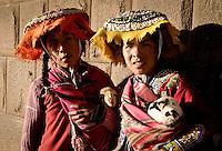 2 young quechua girls holding lambs for tourist photos in Cusco, Peru