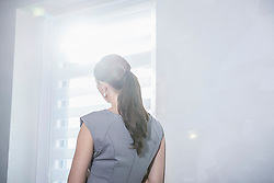Rear view of a businesswoman looking out office window, Munich, Bavaria, Germany