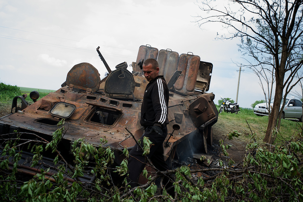 People examine a destroyed armoured personnel carrier in Oktyabrskaya, eastern Ukraine. Pro-Russian militants ambushed Ukrainian troops nearby the day before, killing seven and wounding another eight in the most deadly attack yet on Ukrainian forces.