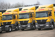 Fleet of yellow DHL heavy goods vehicles parked in the car park of their depot, Martlesham, Ipswich, Suffolk, England