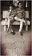 Young couple sit on a park bench together with frustrated expressions, Hanoi, Vietnam, Southeast Asia
