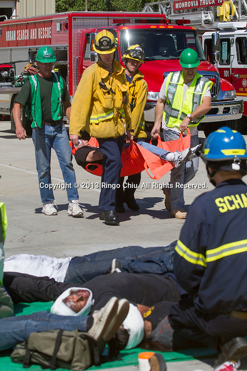 Firefighters and emergency volunteers carry a mock victim during a explosion drill on Thursday, April 18, 2013 at Monrovia Fire Station in Los Angeles, California. The emergency response drill for city staff and trained emergency volunteers. The training included two scenarios, including a response to a damaged reservoir and the buckling of a three-story apartment. (Photo by Ringo Chiu/PHOTOFORMULA.com).