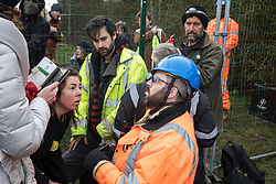 Harefield, UK. 8 February, 2020. Environmental activists seek to calm a HS2 worker who became aggressive when some of them crawled through a ditch under a road closure implemented on Harvil Road in the Colne Valley to facilitate tree felling works for the high-speed rail project. Environmental activists based at a series of wildlife protection camps in the area prevented the tree felling works for the duration of the weekend for which they were scheduled.