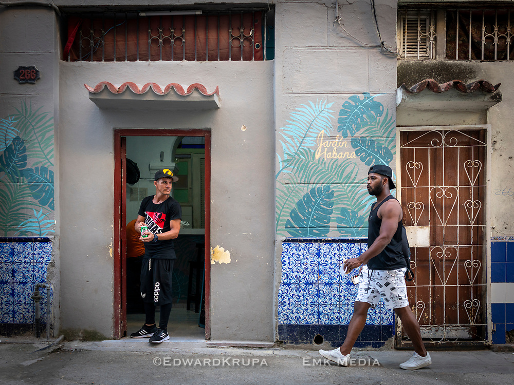 Man opening a beer in a doorway while a man is passing. They are both looking different directions. Havana 2020.
