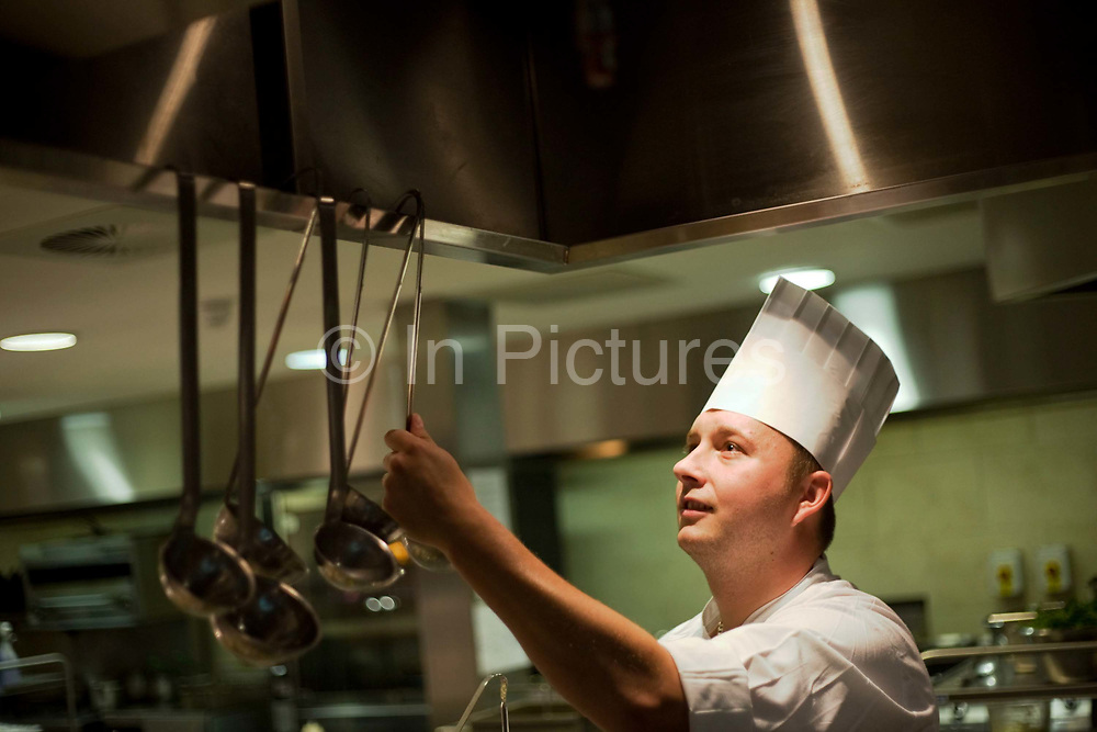 """Showing the face of a man who enjoys his job, a chef reaches for a ladle hanging inside an extractor cover in the kitchens at the Vivre restaurant in Sofitel, a 605 bedroom, 27 suite and 45 meeting room accommodation and business hub Heathrow Airport's hub hotel attached to Terminal 5. The man is wearing a tall chef's hat called a toque and his uniform is pristine to reflect the hygiene standards expected of this luxury hotel and restaurant. From writer Alain de Botton's book project """"A Week at the Airport: A Heathrow Diary"""" (2009)."""
