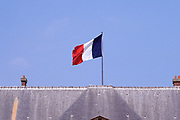 Close up of the tricolor flag of France atop the Invalide Museum in Paris. The Invalide was formerly a military hospital.