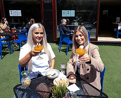 Pictured:  Abbie Sweeney and Joanna Bennett enjoyed the freedom at 56 North as they enjoyed the sunshine.<br /> <br /> Pubs with beer gardens are back in action in Scotland from today.  The Pear Tree and 56 North in Edinburgh asked customers to book socially distanced tables for two-hour slots.  This is to protect staff and customers alike.  All details of booked clients are retained and temperatures taken before anybody is permitted in the Covid 19 free zone. Operations manager for the Pear Tree, Brian Dobie was keen to show customers that the bar was taking their responsibilities seriously with only table service for all food and drink.  Any walk up customers to 56 North have to provide their contact details to ensure any health issues can be traced if required.