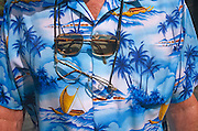 Seen in close-up detail, a holidaymaker's shirt is displayed in Magaluf. He has two pairs of spectacles hanging around his sunburned neck and a printed short-sleeved shirt depicting tropical paradise beach scenes with blue skies, palm trees and representing a Hawaiian Pacific Ocean scene with boats at sea, rolling on the waves. Magaluf is a popular holiday resort on the island of Mallorca, one of the Spanish Balearic Islands. A seedy resort very much orientated around British tourists and catering for both young parties as well as families, Magaluf is considered as an exotic alternative to the chilly seaside towns around the UK's coast.  .