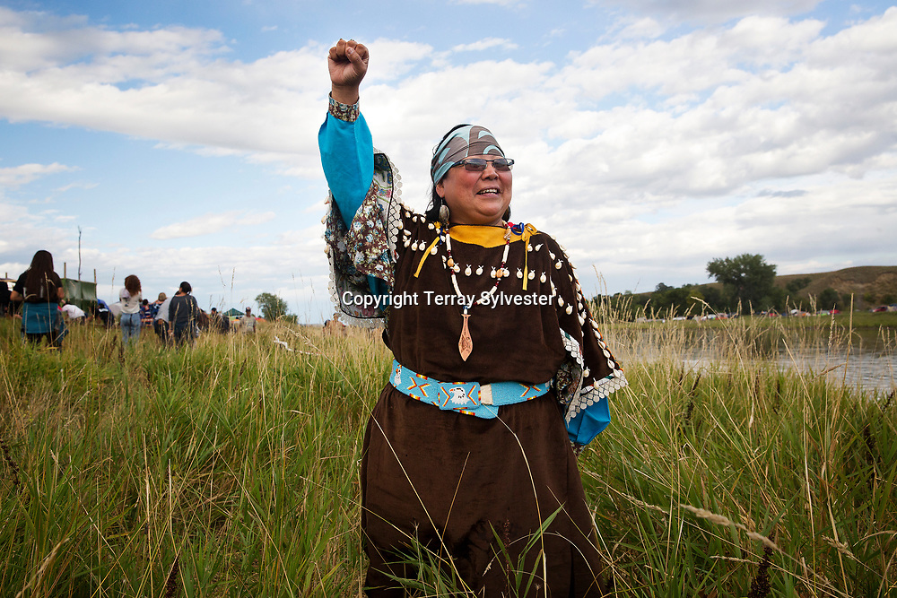 Carol Lawrence of the Warm Springs Indian Nation in Oregon raises a defiant fist while posing for a portrait on the banks of the Cannonball River near the opposition camp against the Dakota Access oil pipeline on September 8, 2016. Cannon Ball, North Dakota, United States.