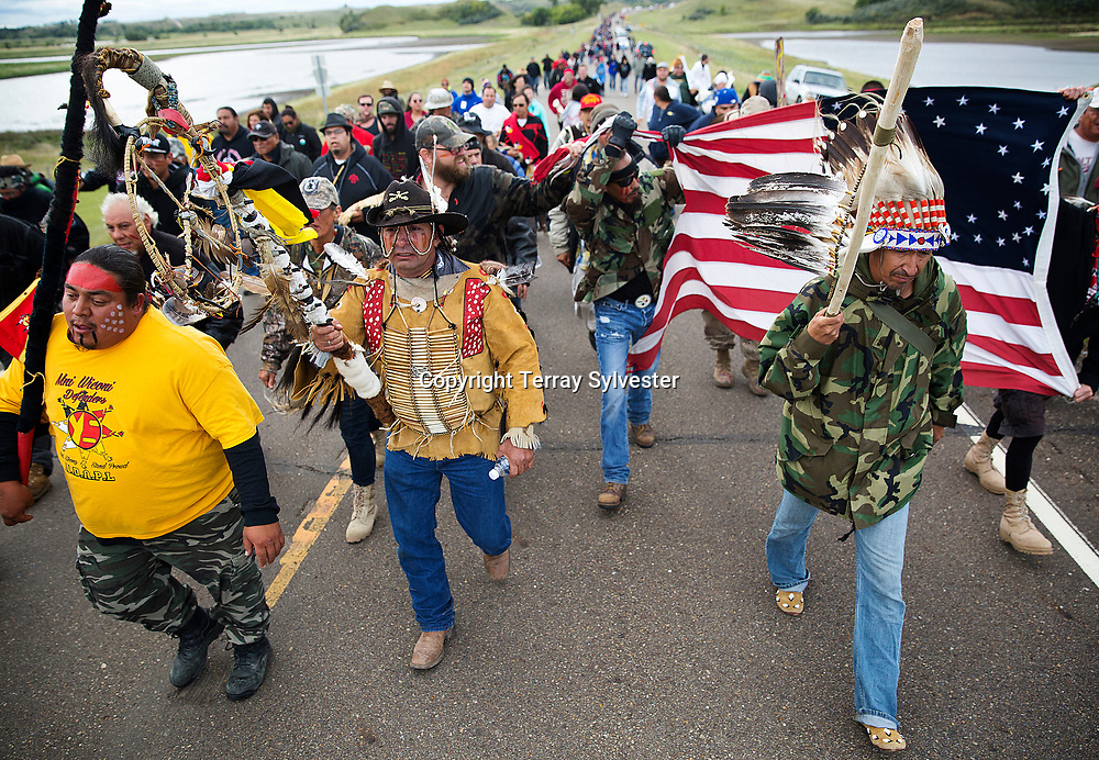 From left, Greg Cournoyer of the Yankton Sioux Tribe, Steven Gray of the Cheyenne River Sioux Tribe, and Catcher Cuts the Rope from the Fort Belknap Reservation in Montana (from left) lead a march to the Dakota Access oil pipeline route on September 9, 2016. Cannon Ball, North Dakota, United States.