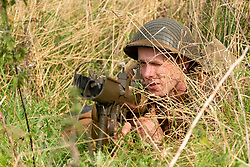 World War 2 Reenactors portray a British Infantry PIAT antitank team from The Duke of Wellingtons Regiment, Polar Division during the second world war as they lay hidden in long grass waiting for German armour. <br /> The PIAT (Projector, Infantry, Anti Tank) was a British man-portable anti-tank weapon developed during the Second World War based on the Spigot Mortar system and had an effective range of 115 yards or 105 meter