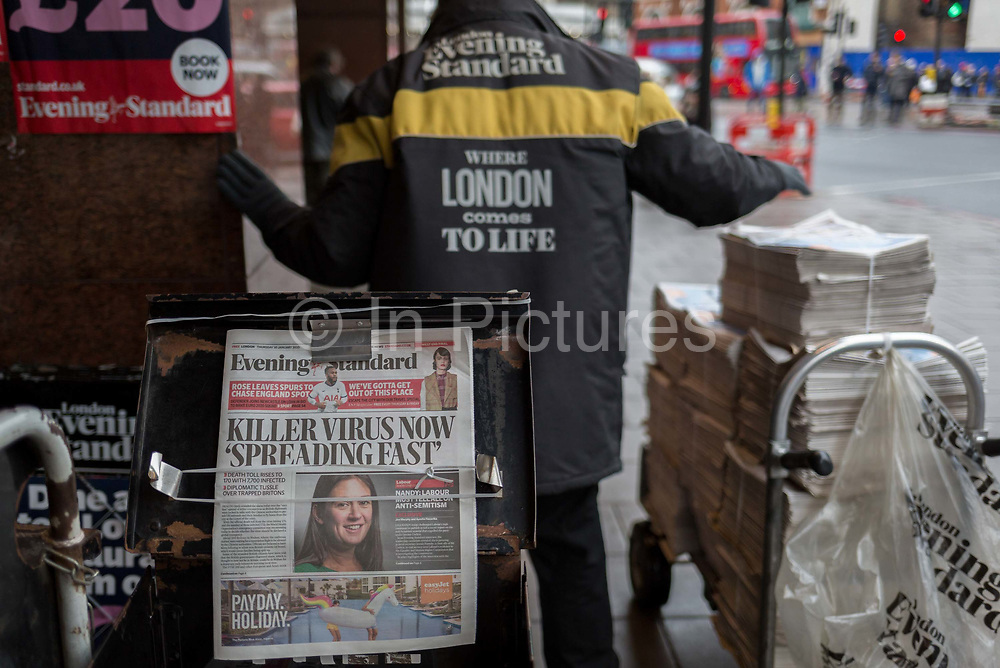 A newspaper vendor unloads more copies of the London Evening Standard newspapers carrying the headline about the latest on the rapid spread of the Chinese-source killer Coronavirus on their front pages, at Victoria station, on 30th January 2020, in London, England.