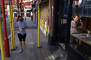 Man talking on his mobile phone as a young man wearing a face mask passes outside as Chinatown remains very quiet with a few people visiting Chinese restaurants to pick up food and to see the red lanterns on 25th June 2020 in London, England, United Kingdom. As the July deadline approaces and government will relax its lockdown rules further, the West End remains quiet, while some non-essential shops are allowed to open with individual shops setting up social distancing systems.