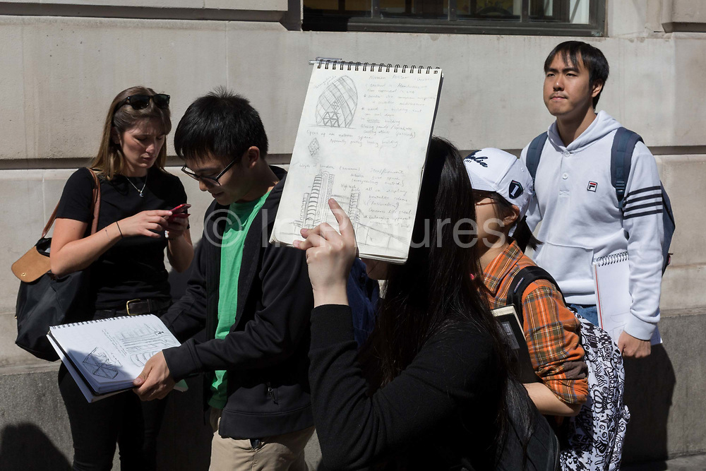 Carrying recent sketches of the Gherkin and the Lloyds of London Building, foreign students of Architecture and the work of Sir Norman Foster, walk through the City of London, the capitals ancient, financial district, on 14th May, in London, England.