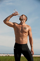Shirtless man drinking bottled water at the beach